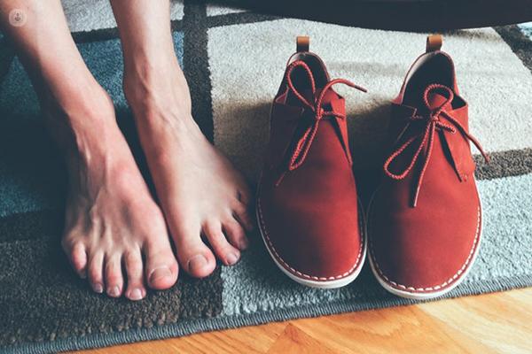 piedi nudi vicino a delle scarpe